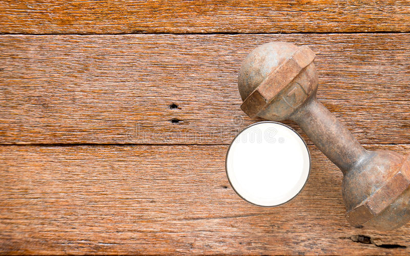 Haltère de fer avec du lait sur le plancher en bois photo libre de droits