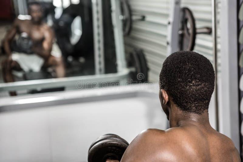 Haltère de levage d'homme sans chemise sur le banc photo libre de droits