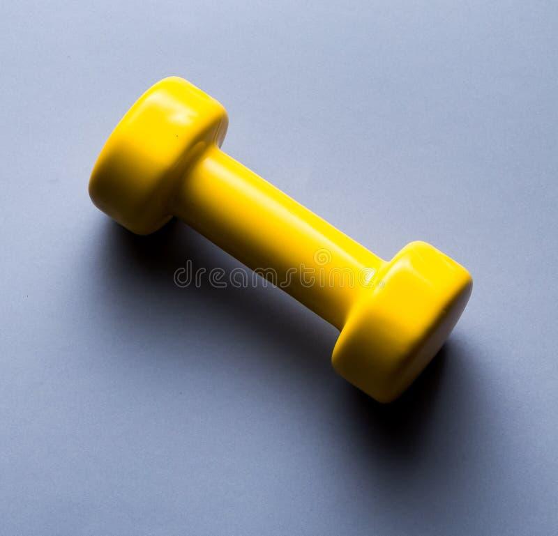Haltère jaune d'isolement sur le fond bleu photos stock