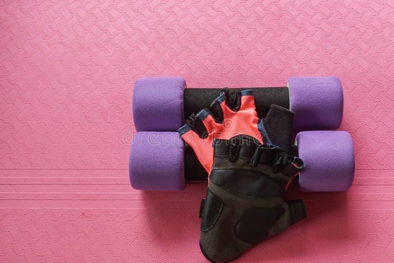 Haltère pourpre avec des gants de forme physique de femmes sur le tapis de yoga pour l'exercice image libre de droits