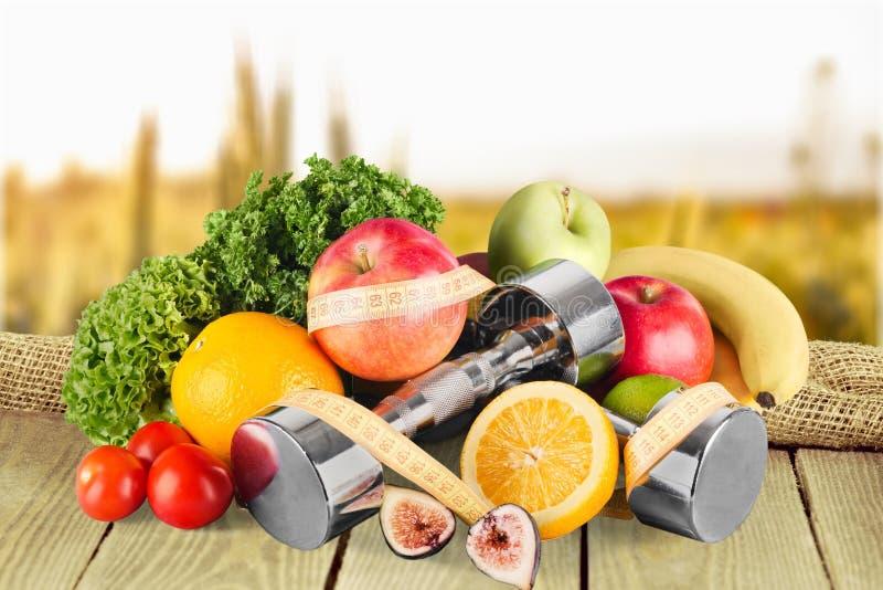 Haltères avec la bande de mesure, légumes et photo stock