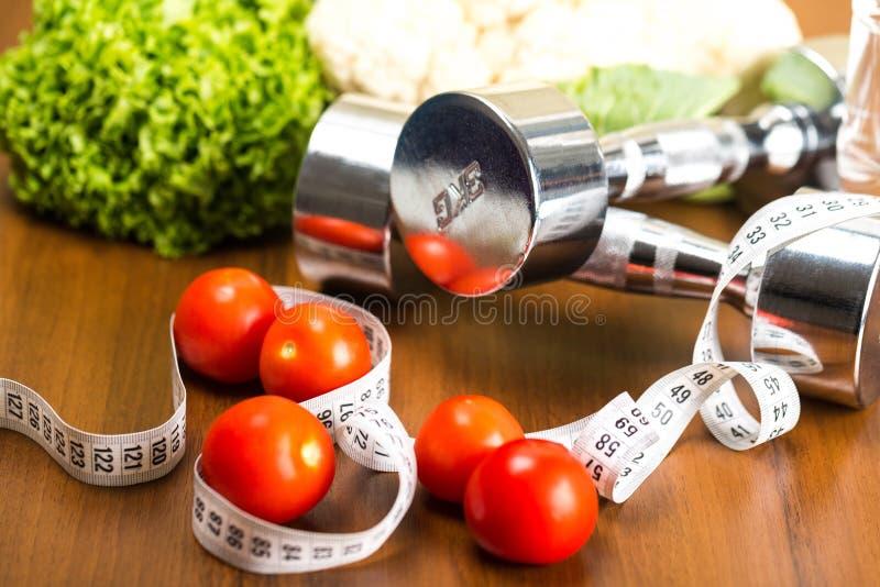Haltères avec la bande de mesure, légumes et photographie stock