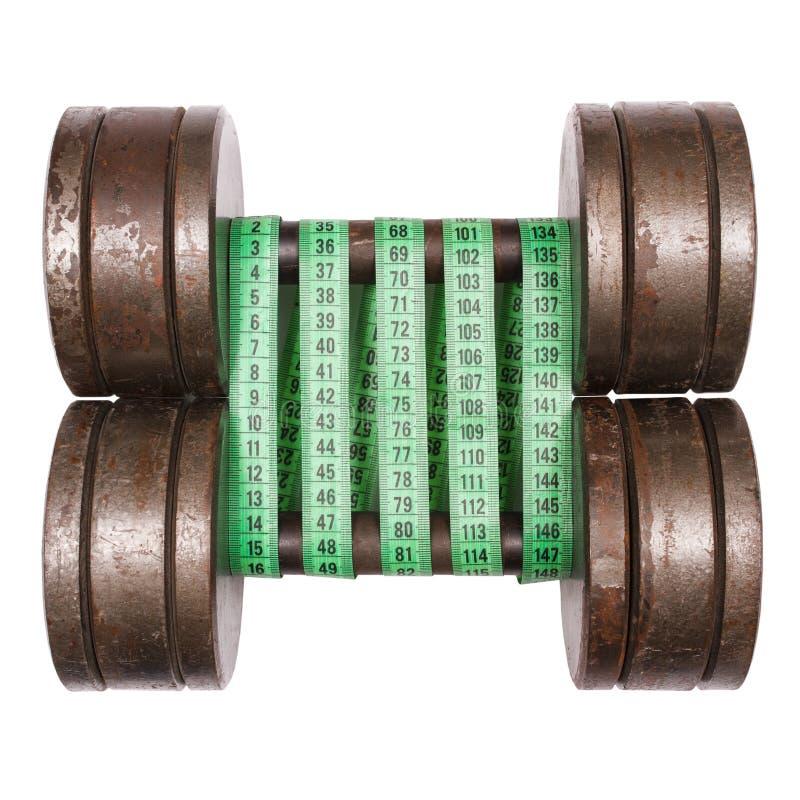Haltères avec la bande de mesure verte sur le blanc photo stock