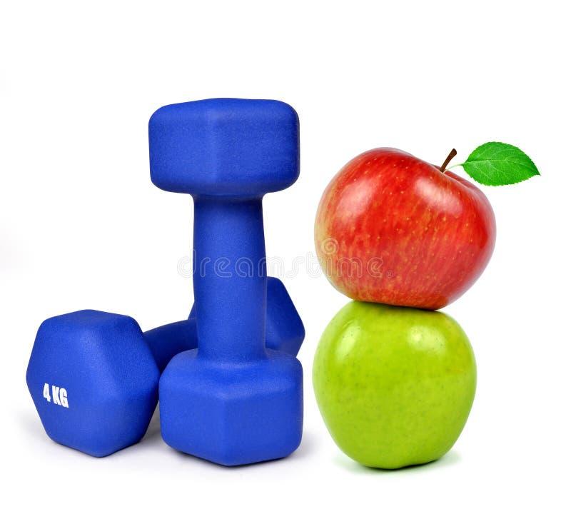 Haltères bleues de forme physique avec des pommes photo stock