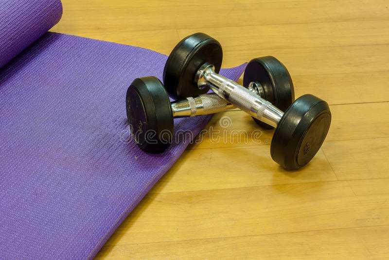 Haltères d'équipement de forme physique, tapis de yoga, sur le fond en bois photo stock
