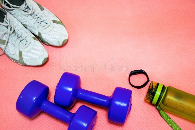 Haltères de Fintes, espadrilles, une bouteille de l'eau et un bracelet de forme physique sur un tapis rose, concept de sports photo stock