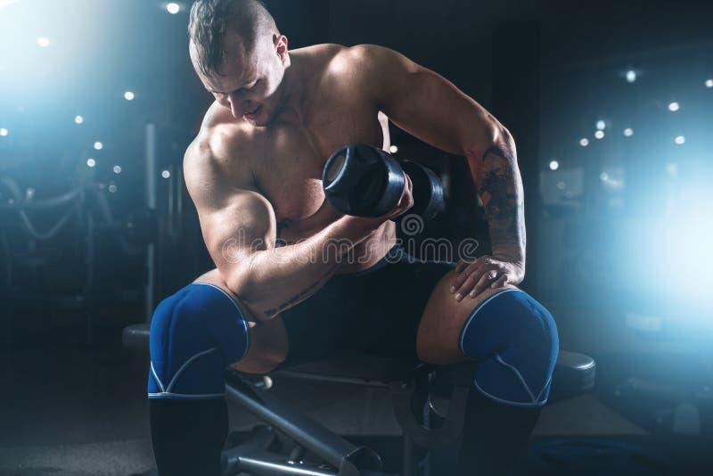 Haltères de levage d'athlète masculin musculaire photographie stock libre de droits