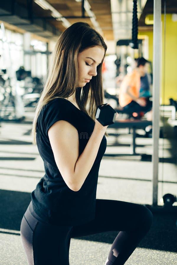 Haltères de levage de belle fille de forme physique Fille sportive de forme physique s'exerçant dans le gymnase photo stock