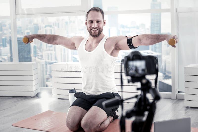 Haltères de levage de joyeux blogger masculin photo stock
