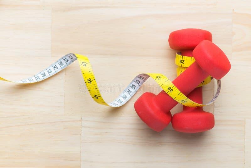 Haltères et bande rouges de mesure pour l'utilisation dans la forme physique, le concept pour amincir et le mode de vie sain Nutr photos stock