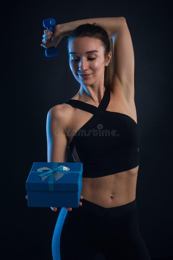 Haltères et boîte-cadeau se tenants blonds sportifs dans des ses mains photo libre de droits