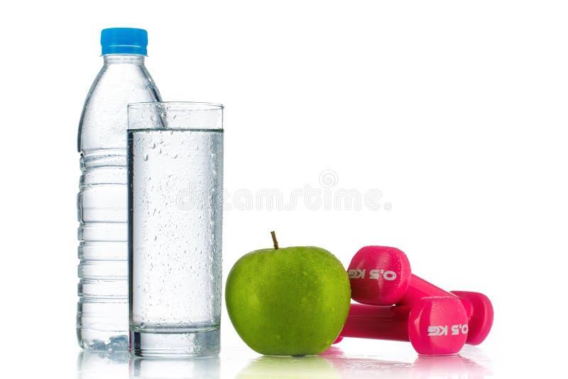 Haltères, pomme verte fraîche et bouteille de l'eau sur le blanc Healt photos stock