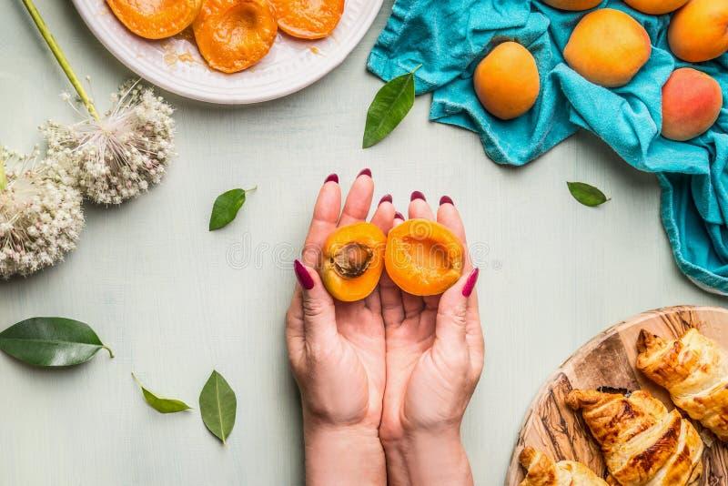 Halt av honhand med halverad aprikos med kernel på lätt köksbord med krossanter och utspridda aprikoser, ovanifrån arkivbild