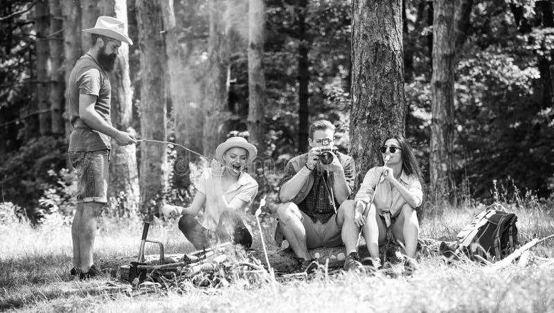 Halt f?r Snack w?hrend des Wanderns Firmenfreunde, die Snackpicknick-Naturhintergrund sich entspannen und haben Kampieren und Wan lizenzfreies stockfoto