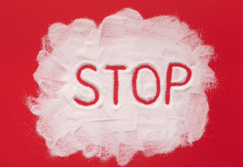 Halt geschrieben auf granulierten Zucker auf rotem Hintergrund stockfotos