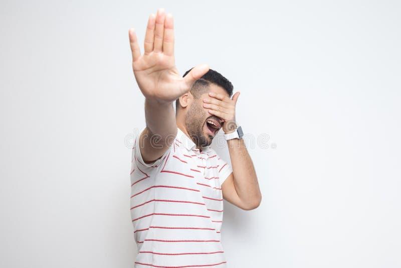 Halt, m?chte ich nicht dieses betrachten Porträt des verwirrten bärtigen jungen Mannes in gestreifter T-Shirt Stellung, seine Aug stockbild