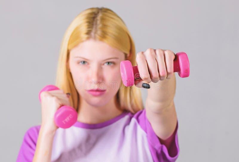 Halt?res de prise de fille Exercices de biceps pour la femelle blanc d'isolement par instructeur de forme physique Concept sain d photo stock