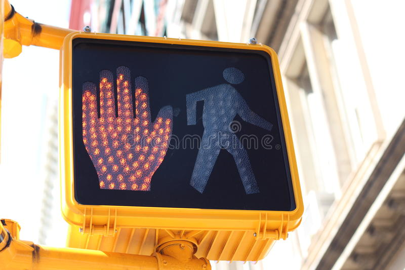 Halt signal on pedestrian crossing. Halt signal with a red hand illuminated on the side of a traffic light at an intersection and pedestrian crossing stock photo