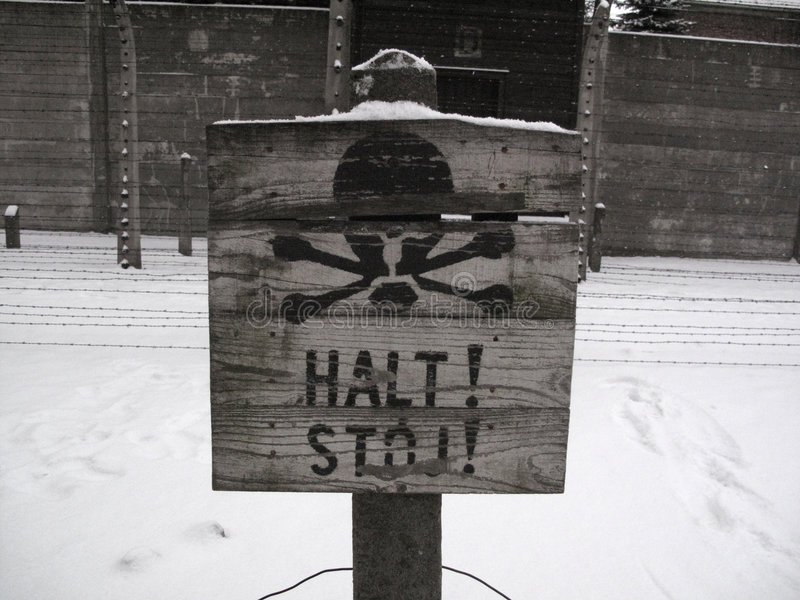 Halt! Stop!. Tablet STOP! infront of barbed wire under tension in Auschwitz royalty free stock photos