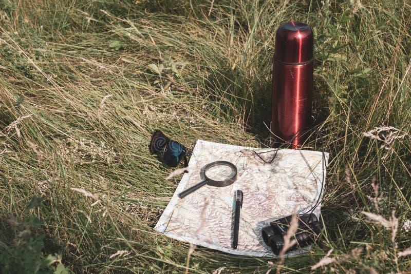 Halt, zum der Karte, des Vergrößerungsglases, der Ferngläser, des Stiftes, der Gläser und der Thermosflasche im Gras stillzustehe stockbild