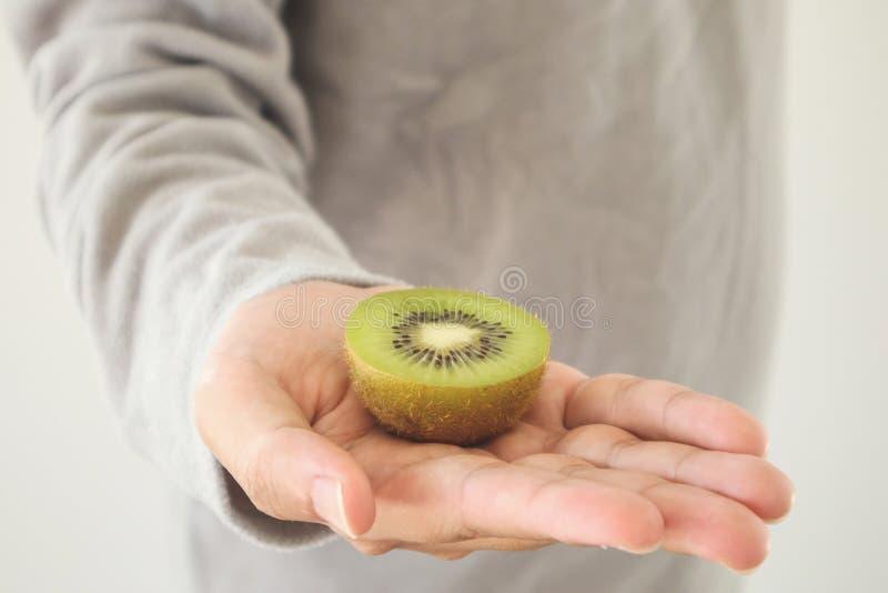 Halten der frischen Kiwi auf Händen lizenzfreie stockbilder