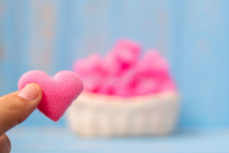 Halten der rosa Herzformdekoration im Korb auf blauem Holztischhintergrund Liebe, Hochzeit, romantisches und glückliches Valentin lizenzfreie stockfotografie