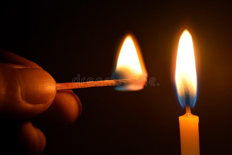 Halten des Matches und des Kerzenfeuers auf schwarzem Hintergrund lizenzfreie stockbilder