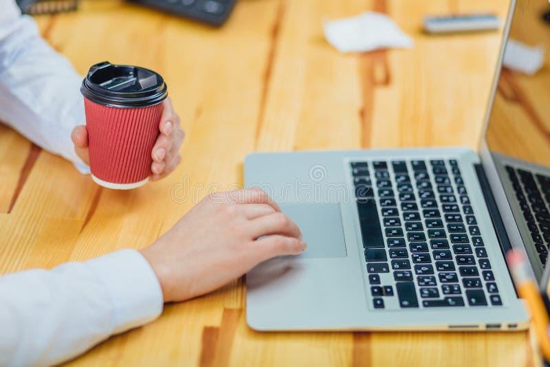 Halten eines jungen Geschäftsmädchens des Kaffees, das für einen Laptop arbeitet Lebensstil von einer modernen Geschäftsfrau unte lizenzfreies stockfoto