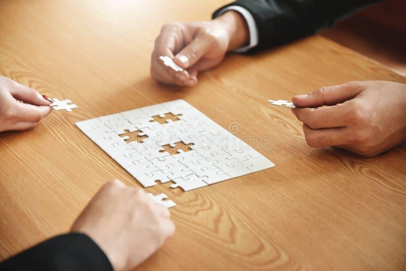 Halten Geschäftsleute Hände Puzzlen lizenzfreies stockfoto