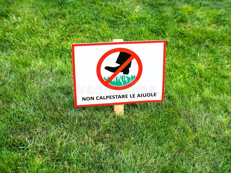 Halten Sie bitte weg vom Rasen, italienischsprachiges herein zu unterzeichnen NICHT CALPESTARE LE AIUOLE stockbilder