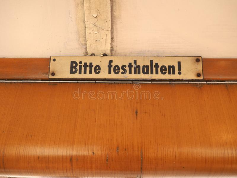 Halten Sie bitte Zeichen auf deutscher Tram stockfotografie