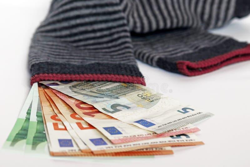 Halten Sie das Geld zu Hause in einem Sparbestand oder investieren Sie es besser in die Bank zu minus Zinsen? stockbild