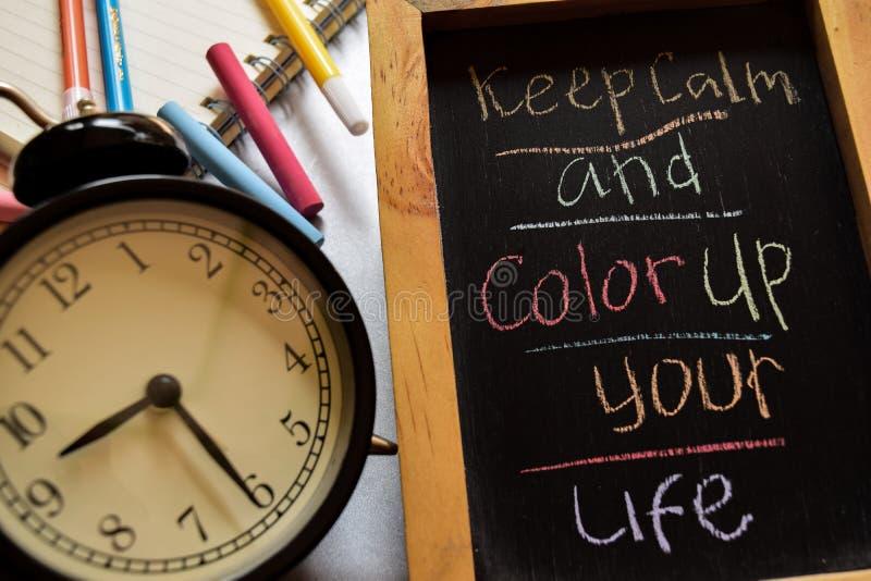 Halten Sie Ruhe und färben Sie herauf Ihr Leben auf buntem handgeschriebenem der Phrase auf Tafel, Wecker mit Motivation und Bild lizenzfreie stockbilder