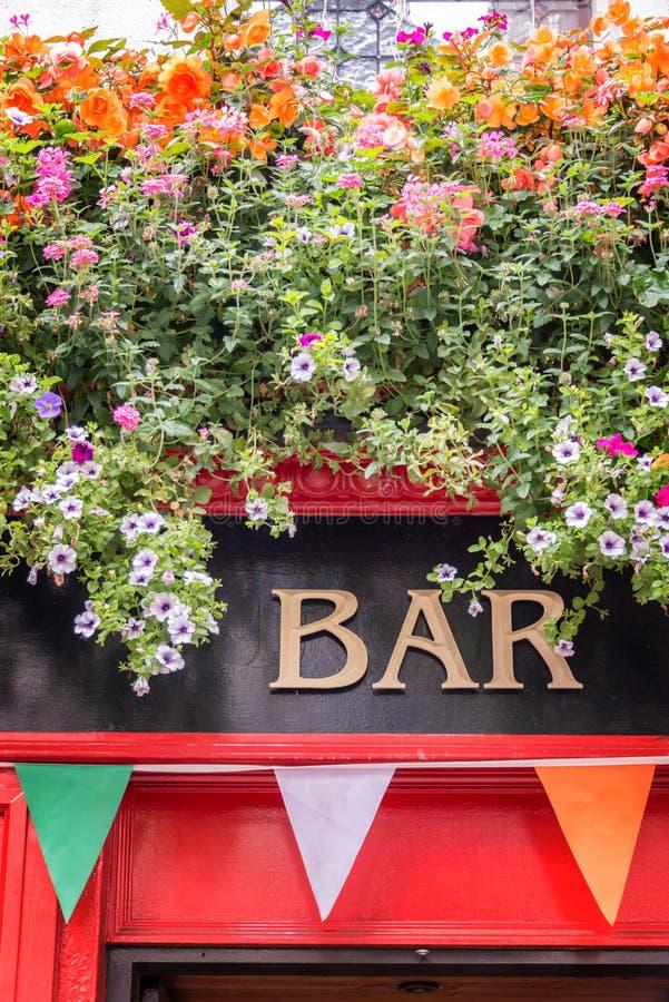 Halten Sie Zeichen mit Blumen und irische Flaggenfarben, irisches Kneipenkonzept in Dublin Ireland ab lizenzfreie stockfotos