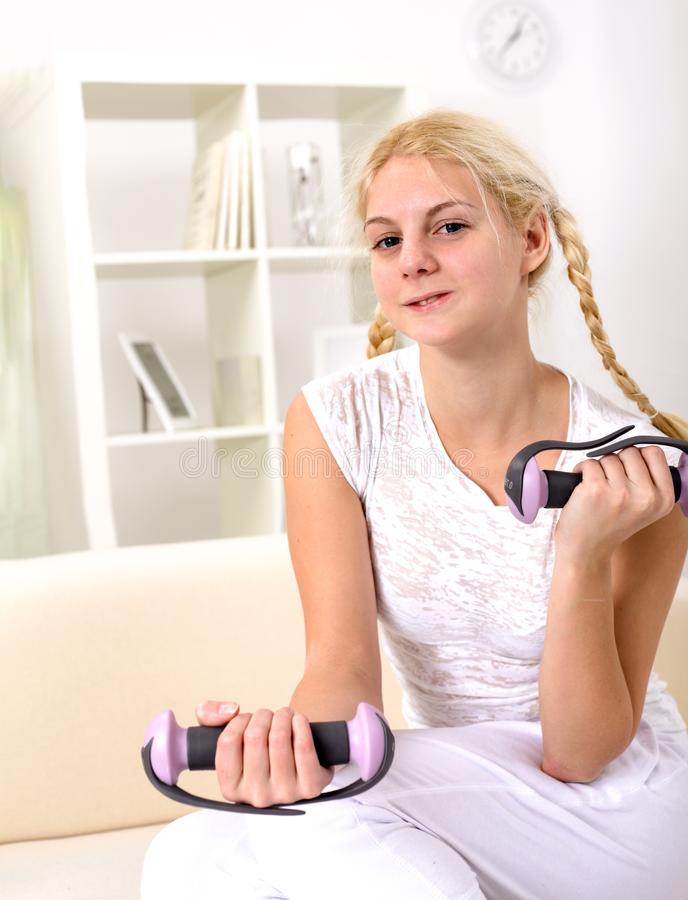 Halterofilismo da menina do adolescente Jovens mulheres bonitas que exercitam com peso em casa fotos de stock royalty free