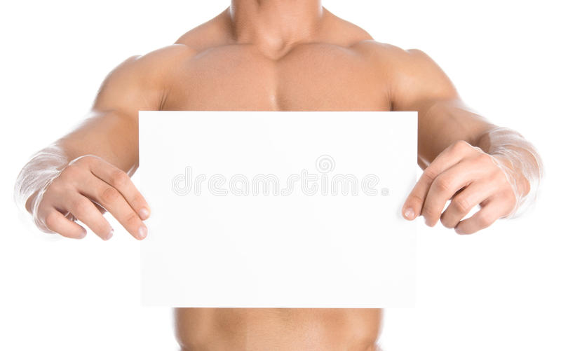 Halterofilismo e propaganda: um halterofilista forte agradável que mantém um cartão vazio branco de papel isolado no fundo branco fotos de stock royalty free