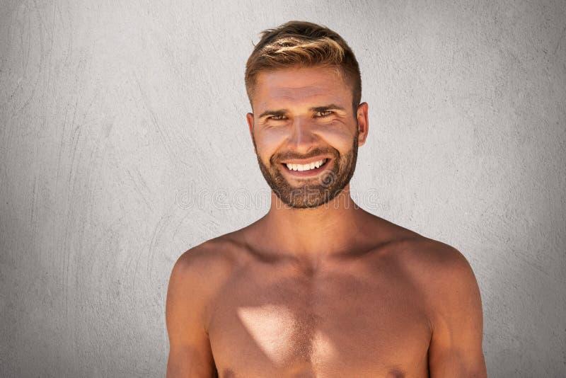 Halterofilista contente com o levantamento do bíceps em topless com sorriso agradável, estando feliz passar o tempo livre no gym  imagem de stock