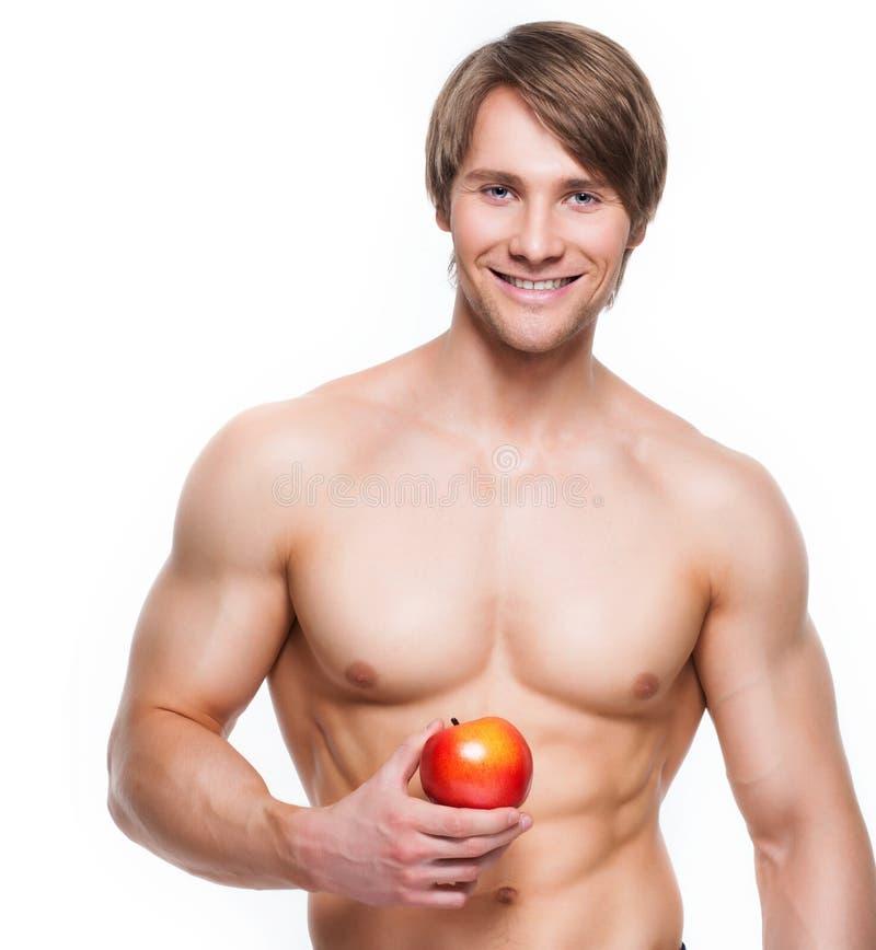 Halterofilista de sorriso novo que guarda a maçã fotos de stock