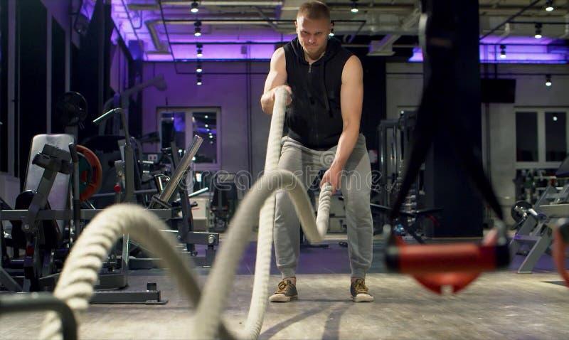 Halterofilista do homem que faz o exercício usando cordas da batalha fotografia de stock
