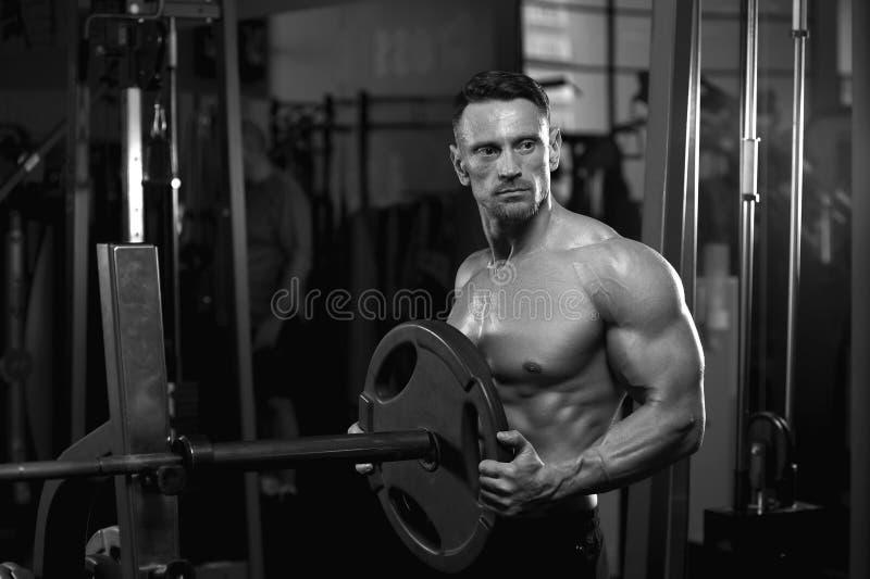 Halterofilista envelhecido meio que guarda pesos no gym imagem de stock