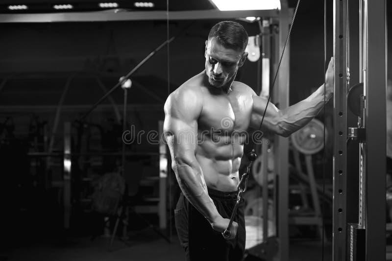 Halterofilista masculino muscular que dá certo na máquina foto de stock royalty free