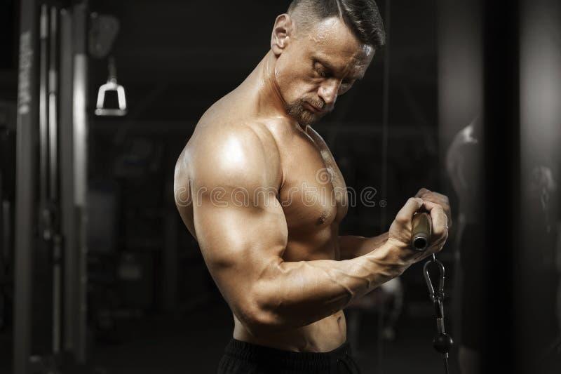 Halterofilista masculino muscular que faz o exercício do tríceps fotografia de stock royalty free