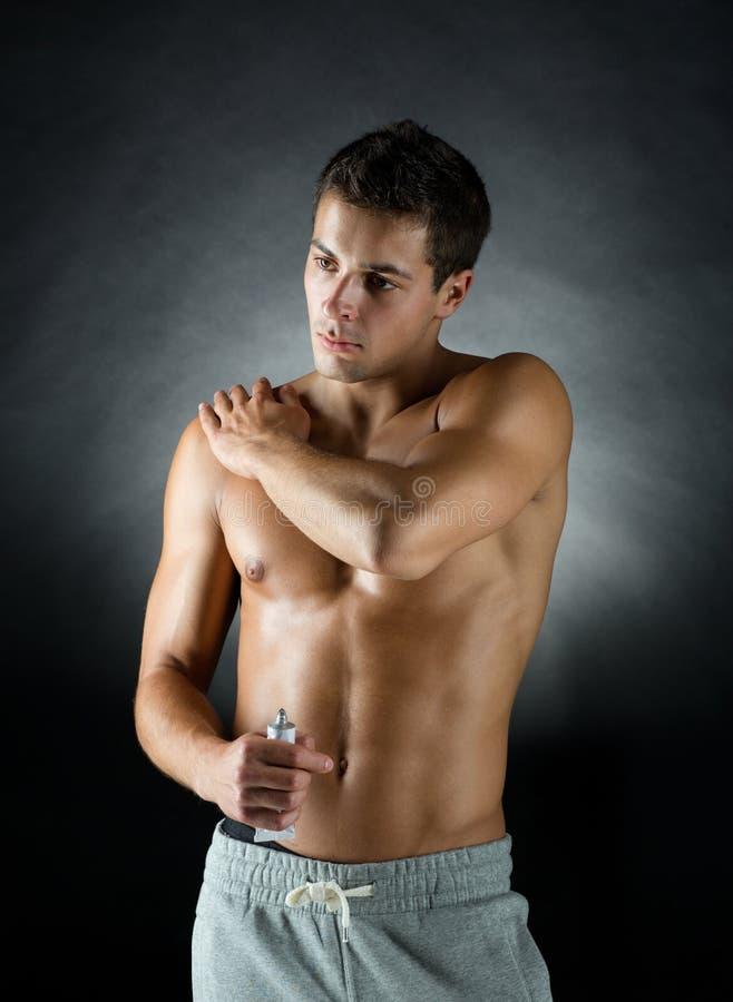 Halterofilista masculino novo que aplica o gel do alívio das dores imagens de stock royalty free