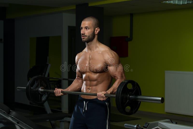 Halterofilista masculino que faz o exercício pesado para o bíceps foto de stock