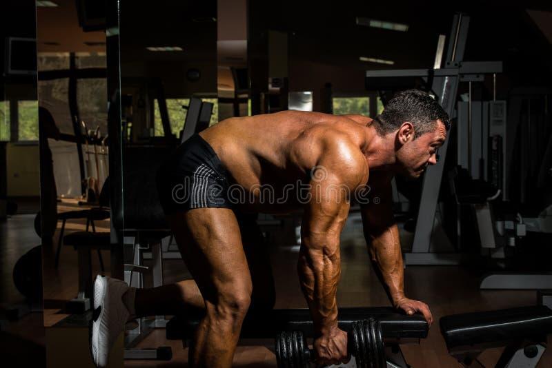 Halterofilista masculino que faz o exercício pesado para a parte traseira imagens de stock royalty free