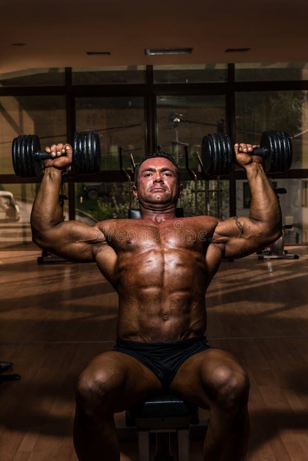 Halterofilista masculino que faz o peso do whit da imprensa do ombro fotos de stock