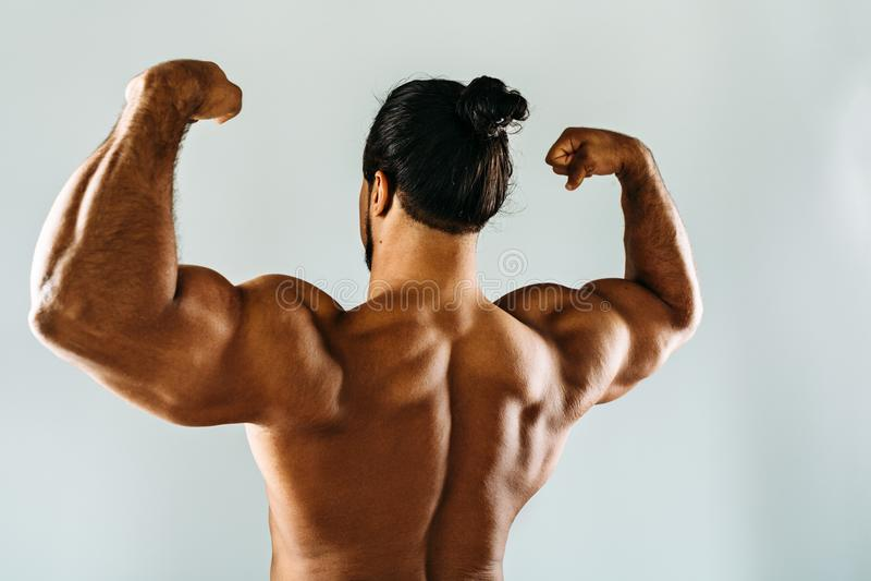 Halterofilista masculino que levanta no estúdio, mostrando o bíceps fotos de stock