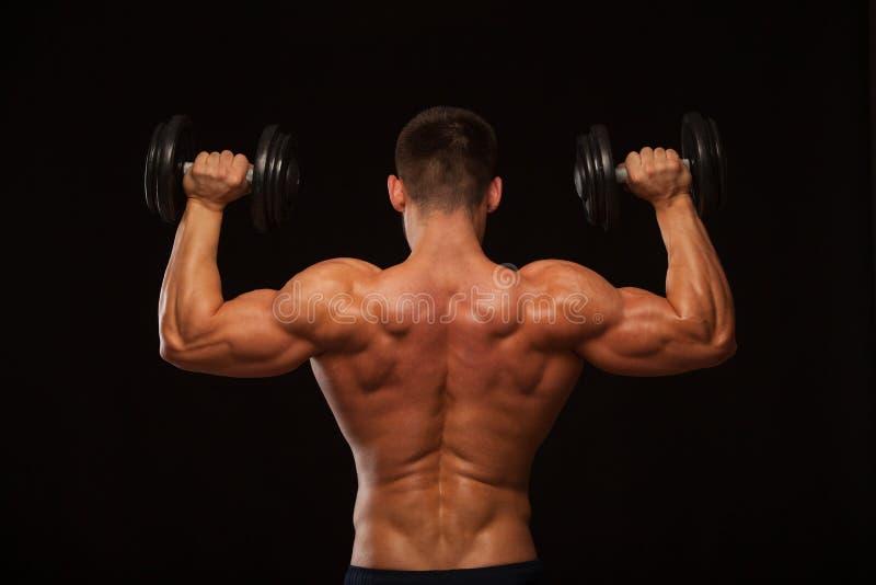Halterofilista modelo masculino muscular que faz exercícios com os pesos, girados para trás Isolado no fundo preto com Copyspace foto de stock
