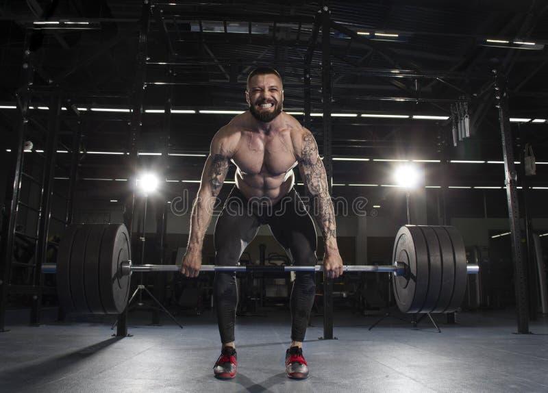 Halterofilista muscular atrativo que faz o exercício pesado do deadlift dentro fotografia de stock royalty free