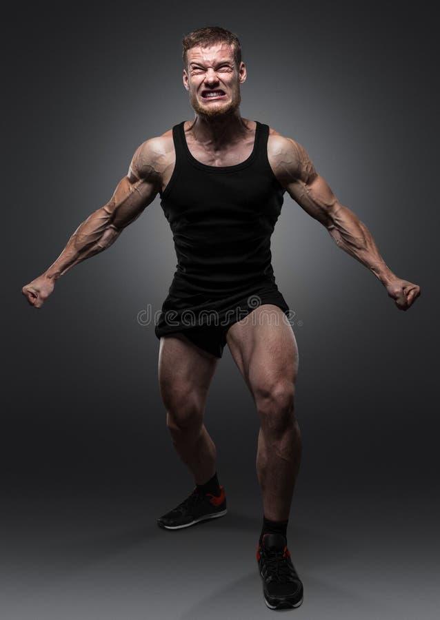Halterofilista muscular novo que levanta sobre o fundo preto imagens de stock